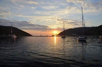 Sailing Greek islands - Greece charter sailing holidays - autumn Sailing - Sailboats anchored near high cliff